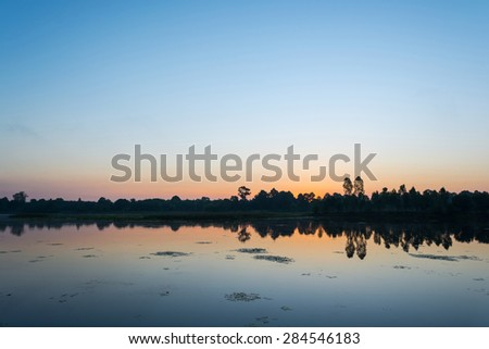 Beautiful sunrise over calm lake. Colorful and vibrant landscape of lake shore. Tranquil landscape useful as background - stock photo