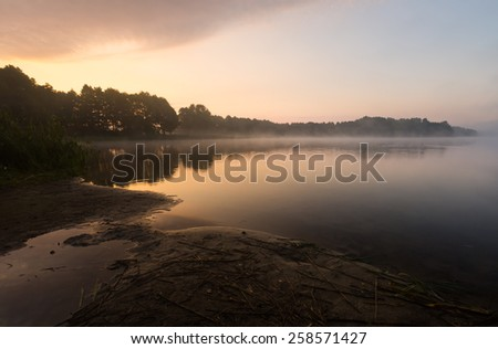 Beautiful sunrise over foggy lake - stock photo