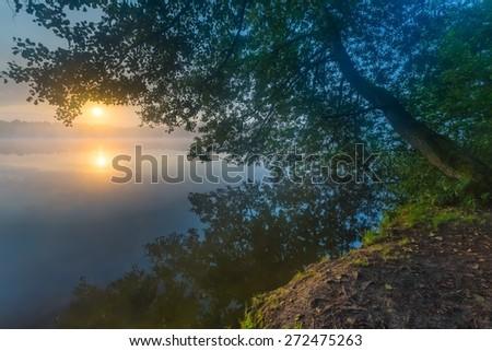 Beautiful sunrise over misty lake. Foggy morning over lake in Mazury lake district, Skanda lake near Olsztyn in Poland. - stock photo