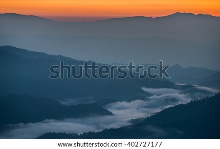 Beautiful sunrise scene with misty in morning in forest valley in Huay Nam Dang National Park. Chiang Mai, Thailand. - stock photo