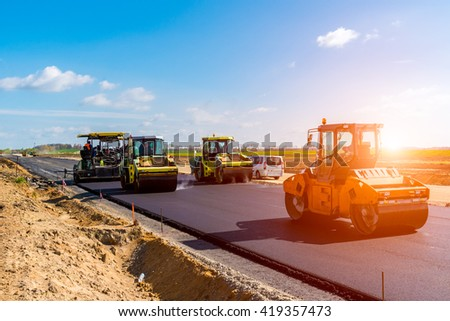 Beautiful sunset above the road roller working on the new road construction site - stock photo