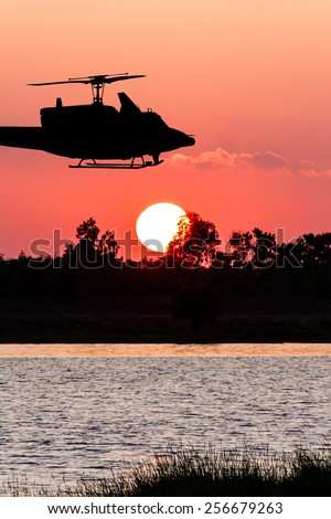 beautiful sunset and Silhouette of helicopter at river - stock photo