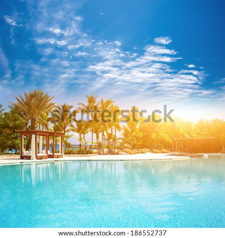 Beautiful sunset at a beach resort in the tropics. Pool at tropical beach - vacation background.  - stock photo