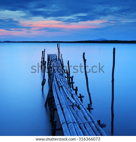 Beautiful sunset at bamboo bridge on sea - stock photo