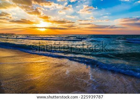 Beautiful sunset at the beach, amazing colors, light beam shining through the cloudscape over the arabian gulf seascape, united arab emirates. Dubai sea and beach - stock photo