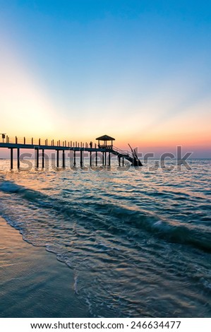 Beautiful sunset at tropical beach with jetty - stock photo