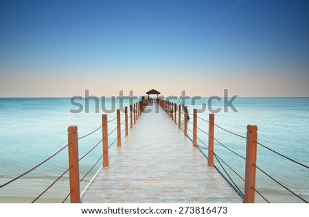 Beautiful sunset at tropical beach with jetty. - stock photo