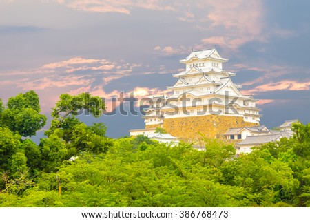 Beautiful sunset behind recently renovated Himeji-jo castle over the tops of trees seen from a distance in Himeji, Japan after 2015 renovations finished - stock photo