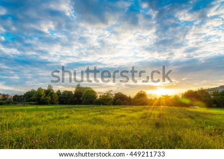 Beautiful sunset landscape over a meadow in evening - colorful sunlight wallpaper - stock photo