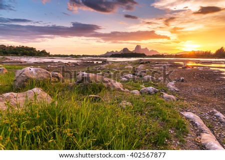Beautiful sunset landscape with mountain and rock - stock photo