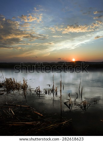 Beautiful sunset on a wild lake. Rainy evening - stock photo