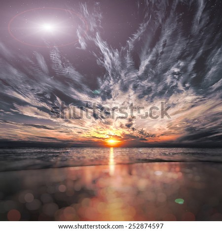 Beautiful sunset on the beach, flash in outer space - stock photo