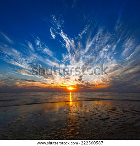 Beautiful sunset on the beach, sunset reflected in calm water - stock photo