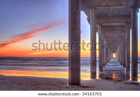 Beautiful sunset on the beach with a concrete pier - stock photo