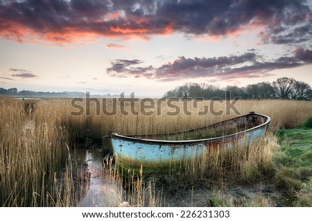 Beautiful sunset over an old rusty fishing boat washed up in reeds on the shores of Poole Harbour in Dorset - stock photo