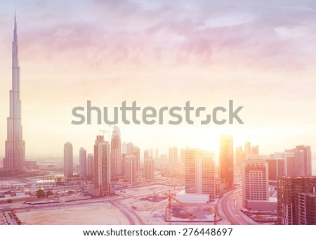 Beautiful sunset over Dubai city, amazing cityscape lit with warm sun light, contemporary new modern architecture, view from above on a luxury property of United Arab Emirates - stock photo