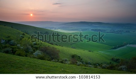 Beautiful sunset over English countryside landscape with light across hilltops - stock photo