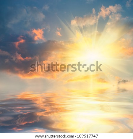 Beautiful sunset over sea with reflection in water, colorful clouds in the sky - stock photo