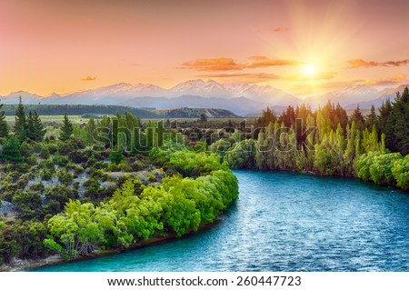 Beautiful sunset over the bend of the river Clutha with Southern Alps peaks on the horizon, New Zealand - stock photo