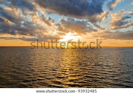 beautiful sunset over the smooth surface of a mountain lake - stock photo