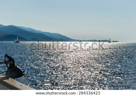 Beautiful sunset seen from sailing boat, with shining sea, yachts and mountains. Summer background - stock photo