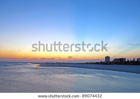 Beautiful sunset taking over the coastline in Siesta Key Beach, Florida. - stock photo