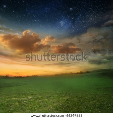 beautiful sunset with a green meadow - stock photo