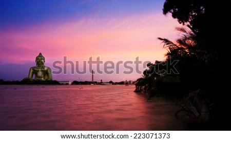 Beautiful sunset with Buddha statue - stock photo