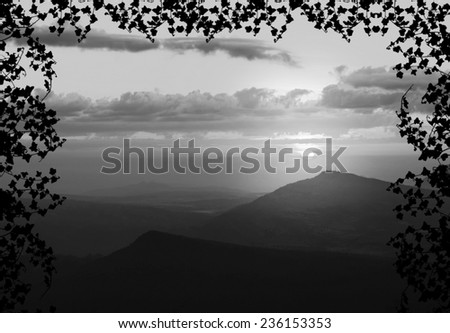 Beautiful sunset with cloud and mountain,tree foreground siluette frame,gray color tone - stock photo