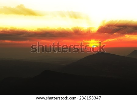 Beautiful sunset with cloud and mountain with sunray,orange color tone - stock photo