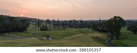 Beautiful sunset with lush greenery at golf course.