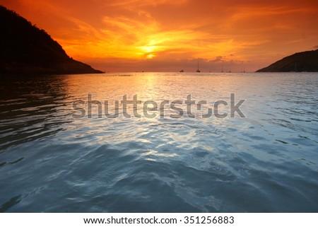 Beautiful sunset with orange sky over blue sea - stock photo