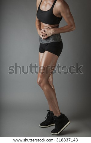 Beautiful super fit young woman showing off her perfect muscular body. Fitness model. Perfect Slim Body. Studio shot - stock photo