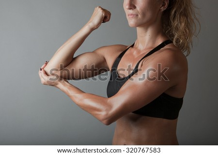 Beautiful super fit young woman showing off her perfect muscular body. Fitness model. Perfect Slim Body with sturdy biceps. Studio shot - stock photo
