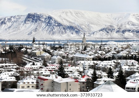 Beautiful super wide-angle aerial view of Reykjavik, Iceland in winter with harbor and skyline mountains and scenery beyond the city, seen from the observation desk in Perlan.  - stock photo
