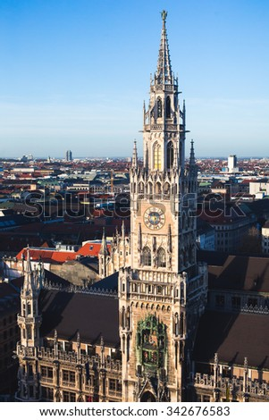 Beautiful super wide-angle sunny aerial view of Munich, Bayern, Bavaria, Germany with skyline and scenery beyond the city, seen from the observation deck of St. Peter Church  - stock photo
