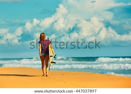Beautiful surfer girl is enjoying vacation on the tropical beach. Young woman with surfboard in Sri Lanka.  - stock photo