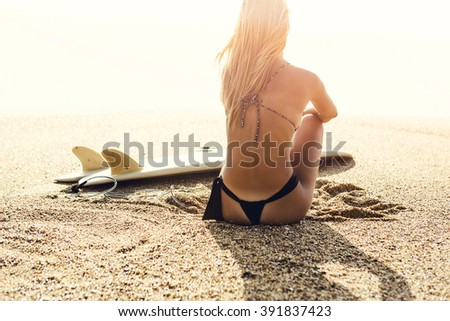 Beautiful surfer girl sitting on the beach and checking the waves - stock photo