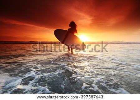 Beautiful surfer woman on the beach at sunset - stock photo
