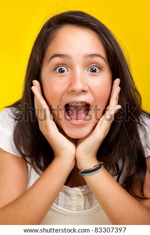 Beautiful surprised brunette teenage girl isolated in yellow background. - stock photo