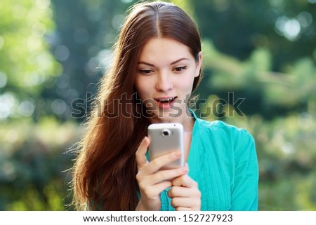 beautiful surprised young woman using mobile, sitting in park, smiling - stock photo
