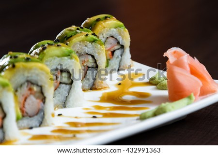 beautiful sushi roll topped with avocado stuffed with crab meat garnished with a sweet sauce and sesame seeds - stock photo