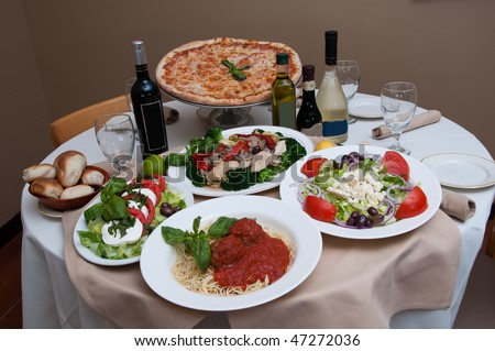 beautiful table of italian salads, pasta, pizza and drinks - stock photo