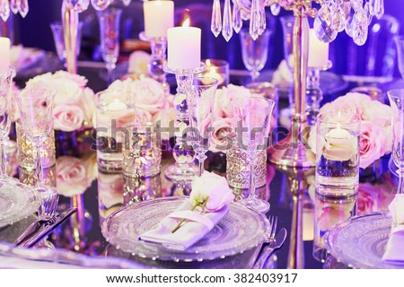 Beautiful table set with candles and flowers for a festive event, party or wedding reception, in purple light - stock photo