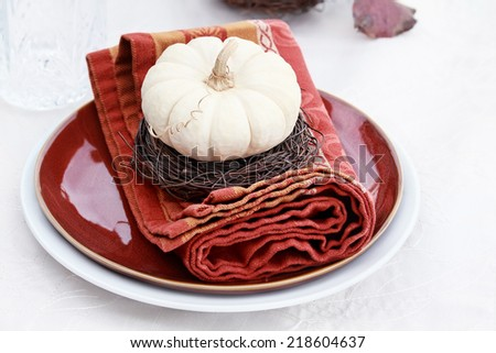 Beautiful table set with white pumpkins and natural items ready for an autumn meal. - stock photo