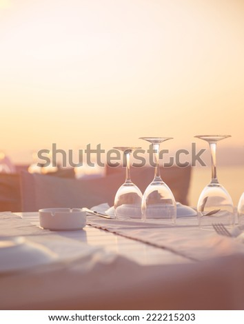 Beautiful table setting on the beach, beautiful crystal wine glasses for romantic wedding celebration, luxury event concept - stock photo