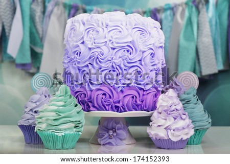 Beautiful table with cake and cupcakes in aqua and purple - stock photo