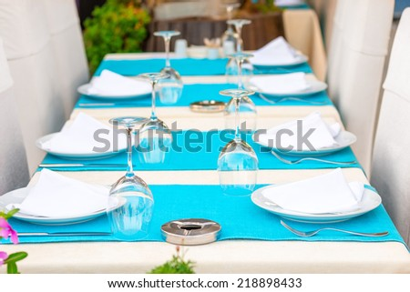 Beautiful tables with kitchenware in a summer cafe - stock photo