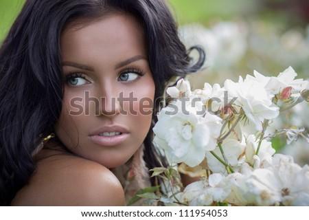 Beautiful tanned brunette posing near white roses - stock photo