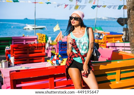 Beautiful tanned cheerful funny cheeky hipster girl on the background of the sea, the ocean, the beach bar, enjoying the sun, dressed in casual clothes, a plaid shirt, pink hat striped backpack - stock photo